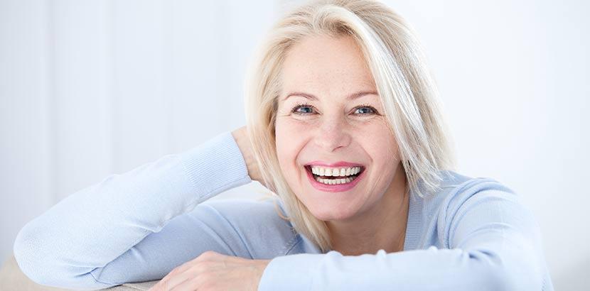 Attraktive silberhaarige Frau mittleren Alters, die es geschafft hat, ihre Wechselbeschwerden dauerhaft zu lindern.