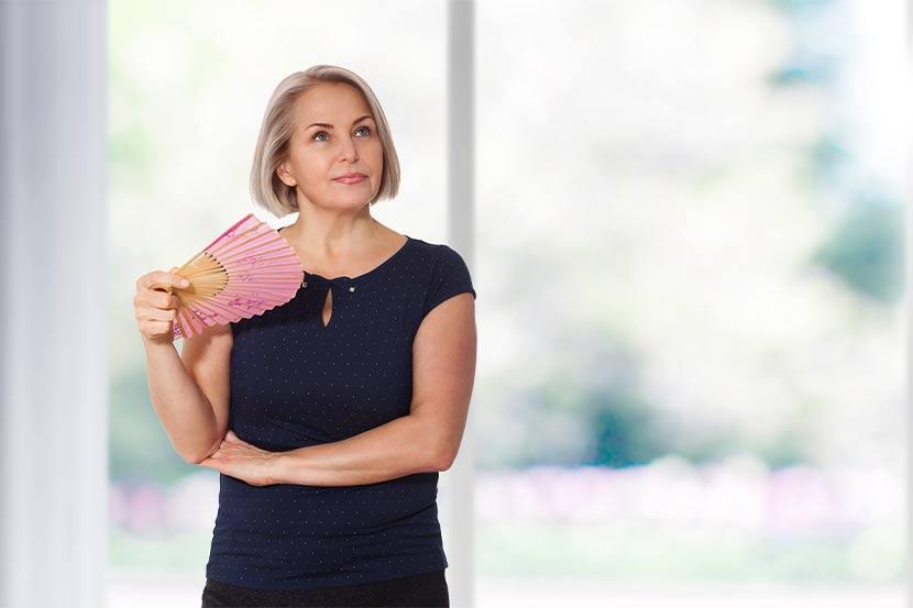 Hübsche Frau mittleren Alters mit Fächer, die wissen will, wie sie ihre Wechselbeschwerden lindern kann.
