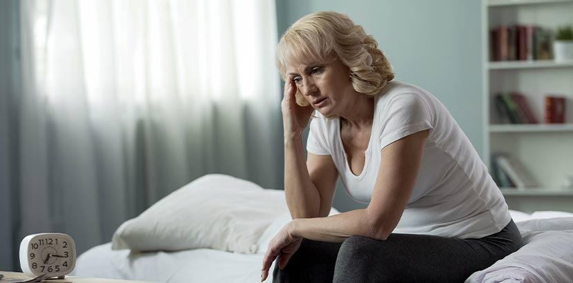 Frau mittleren Alters, die unter starken Wechselbeschwerden leidet.