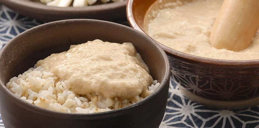 Brei aus Yamswurzel auf Reis in einer Holzschüssel.