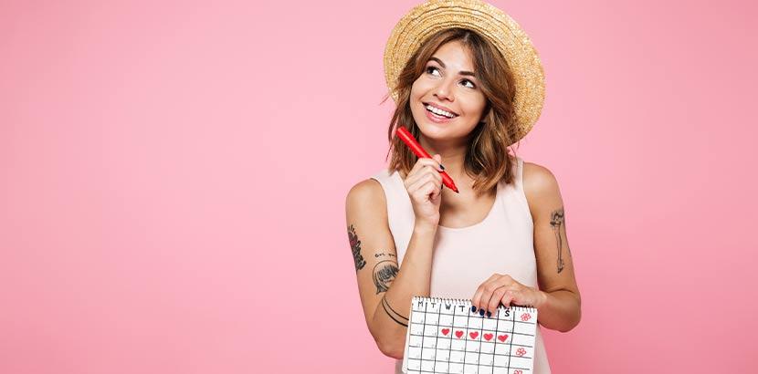 Junge Frau mit Kalender, in dem sie ihren Zyklus notiert hat. Yamswurzel.