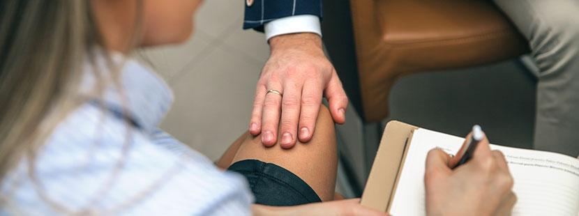 Junge Frau, die von ihrem Chef sexuell belästigt wird. Mobbing am Arbeitsplatz, Hand auf Knie.