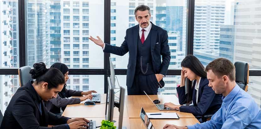 Älterer Firmenchef im Meeting mit jüngeren Mitarbeitern; Mobbing am Arbeitsplatz, Bossing