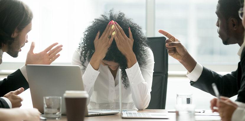 Junge Frau, die während eines Meetings von Kollegen gemobbt wird.