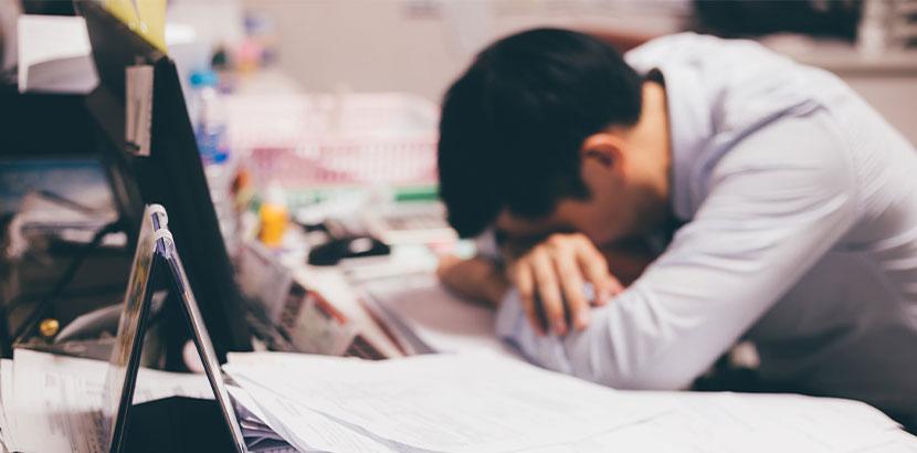 Überforderter junger Mann, der am Schreibtisch zusammenbricht wegen Mobbing am Arbeitsplatz.
