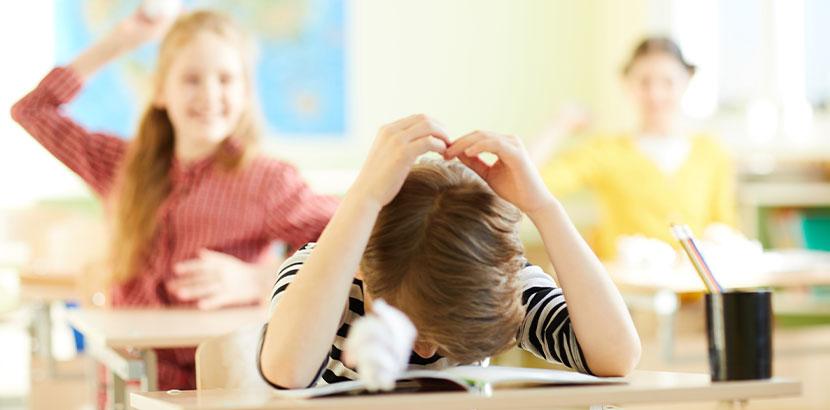 Junge, der in der Schule von Mitschülerinnen mit Papierkugeln beworfen wird. Mobbing in der Schule.