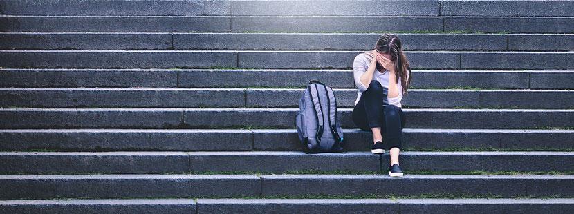 Mädchen weint in der Schule alleine auf einer Treppe. Mobbing in der Schule.