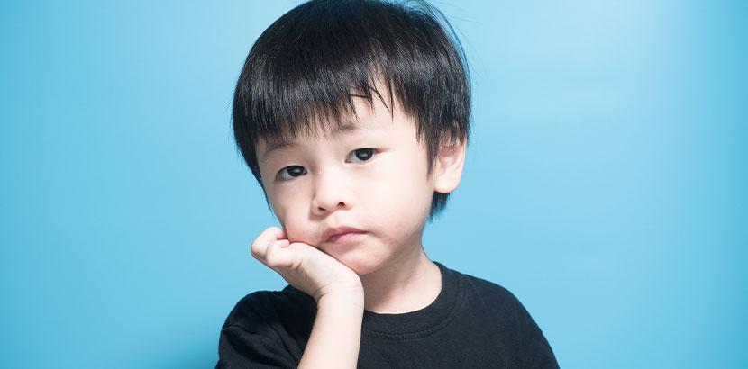 Kleiner Junge mit Mumps, der sich die Backe hält. Mumps Symptome.