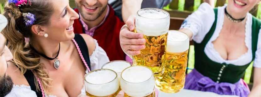Gruppe von Frauen und Männern, die auf der Wiener Wiesn 2019 mit Biergläsern anstoßen.