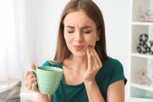 Junge Frau mit schmerzempfindlichen Zähnen, die ihren Zahnschmelz aufbauen muss.