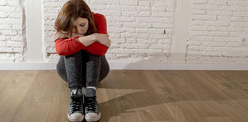 Teenager Mädchen, das schwanger und verzweifelt am Boden sitzt. Abtreibung Wien Kosten.