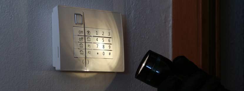 Taschenlampe, die in einem dunklen Raum auf eine Alarmanlage leuchtet. Alarmanlagen Wien.