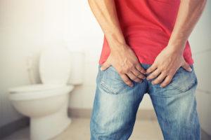 Junger Mann, der vor der Toilette steht, und sich sein schmerzendes Hinterteil hält. Analfissur Heilung.