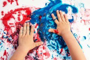 Ergotherapie Kinder: Kind malt mit Farben