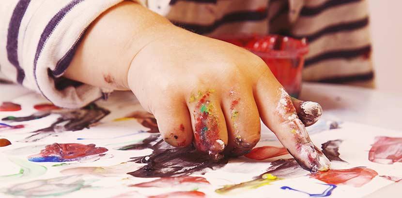 Ergotherapie bei Kindern - Kind malt auf Papier mit Farben