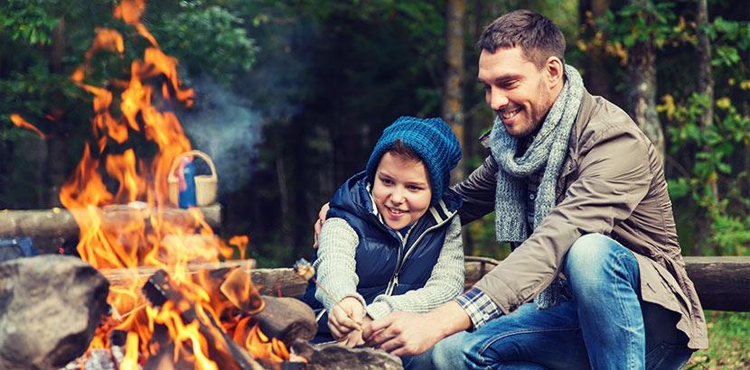 Vater und Sohn, die Marshmallows über dem Lagerfeuer rösten. Geschenke für 9 Jährige Jungs.