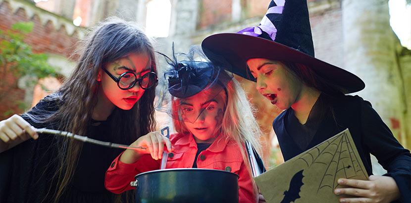 Drei neunjährige Mädchen in Hexen-Kostümen. Geschenke für 9-jährige Mädchen.