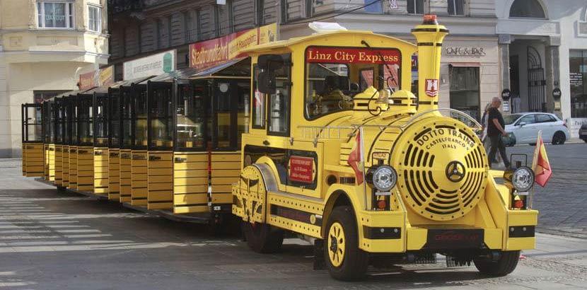 Der gelbe Miniaturzug Linz City Express vor der Abfahrt. Schlechtwetterprogramm Linz