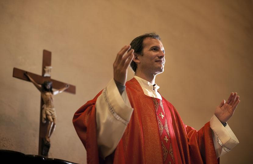 Ein katholischer Pfarrer predigt vor einem Kreuz.