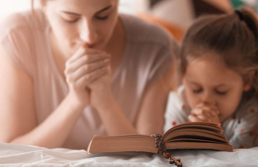Eine Taufpatin und ihr Patenkind lesen die Bibel und beten zusammen.