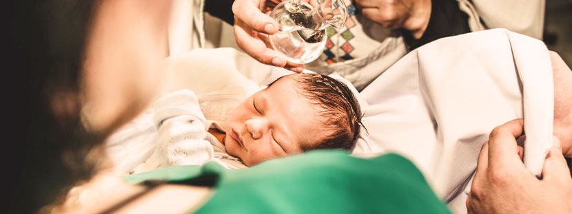 Ein Baby wird von einem Pfarrer mit Taufwasser getauft.