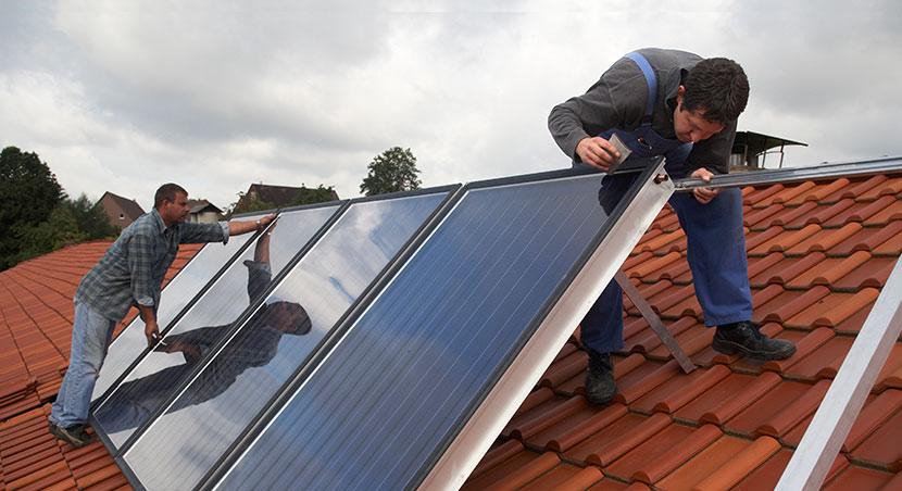Zwei Installateure montieren Sonnenkollektoren für eine Solarthermieanlage auf einem Dach.