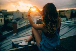 Eine Frau sitzt auf dem Dach, während die Sonne untergeht.