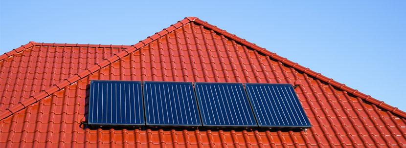 Sonnenkollektoren auf einem roten Hausdach