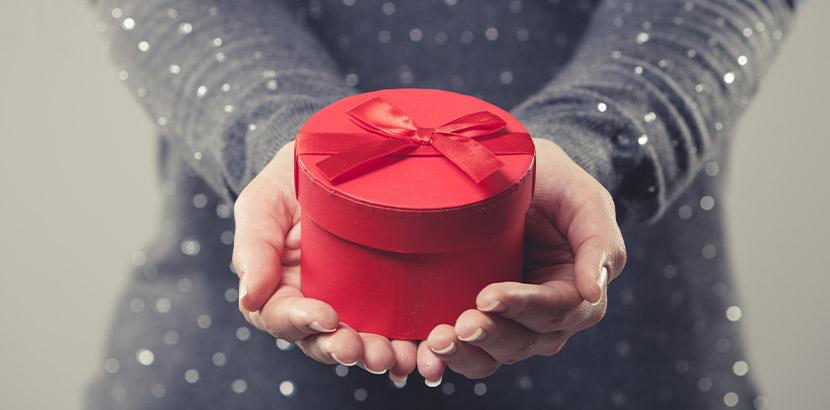 Frau im grauen Kleid, die eine rote Geschenkbox mit einem außergewöhnlichen Geschenk in die Kamera hält.