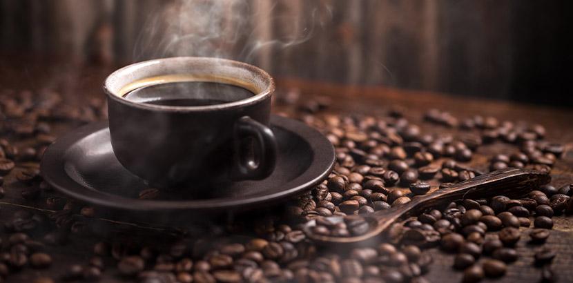 Eine Tasse Kaffee inmitten von gerösteten Kaffeebohnen. Außergewöhnliche Geschenke.