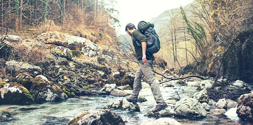 Junger Mann mit Wanderrucksack, der einen Fluss überquert. Außergewöhnliche Geschenke.