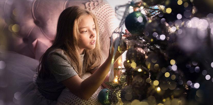 Hübsches blondes Mädchen, das Christbaumkugeln aufhängt. Geschenke für Teenager.
