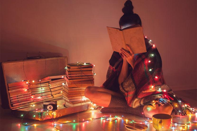 Teenager Mädchen, das sich hinter einem Buch versteckt und eine Lichterkette um sich gelegt hat. Geschenke für Teenager zu Weihnachten.