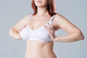 Junge Frau mit großen natürlichen Brüsten, die über eine Brustverkleinerung nachdenkt. Grauer Hintergrund.