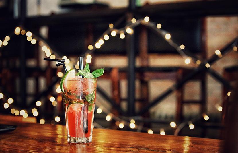 Ein Glas mit einem roten Cocktail auf einer Theke. Cocktailbar Linz