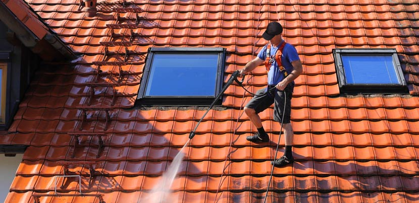Ein Mann, der bei einer professionellen Dachreinigung mit dem Hochdruckreiniger auf dem Dach steht