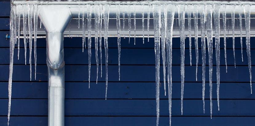 Eis auf der Dachrinne von einem Gebäude, das verhindert werden soll.