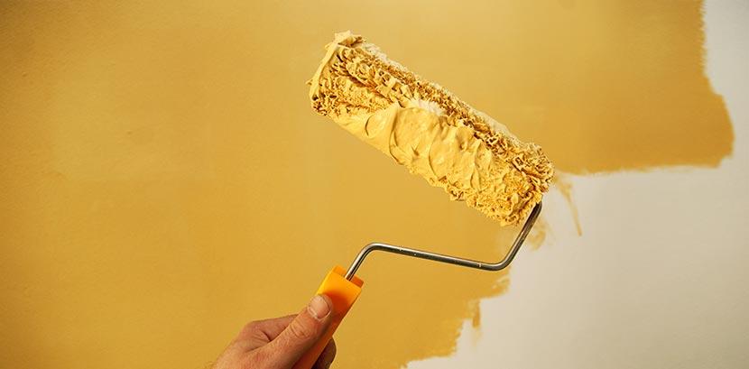Eine Langflorrolle mit gelber Farbe, mit der eine Decke gelb gestrichen wird.