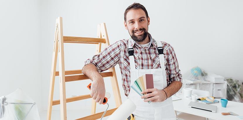 Ein Maler lehnt lächelnd an einer Leiter und hält einen Farbfächer in die Kamera