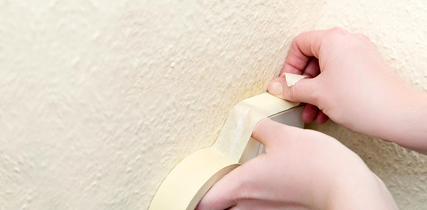 Zwei Hände kleben vor dem Decke Streichen eine Wand mit Malerkrepp ab.