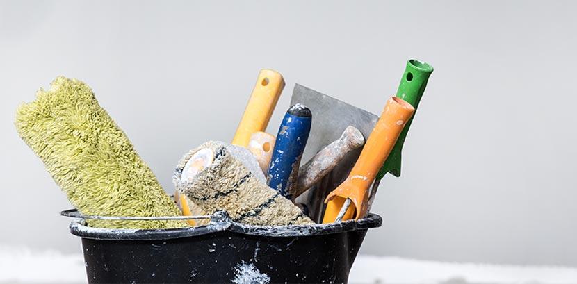 Ein Kübel mit schmutzigen Pinseln und Malerrollen.