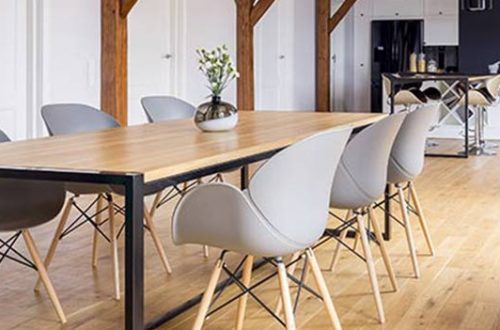 Ein Raum mit einem großen Holztisch, modernen, hellgrauen Stühlen und einem hellen Dielenböden.