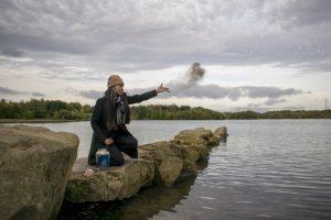 Ältere Frau mit langen schwarz-grauen Haaren, die an einem Herbsttag am Meer sitzt und die Asche eines verbrannten Menschen in den Wind streut. Feuerbestattung Wien Kosten.
