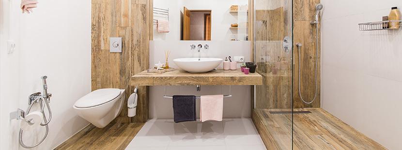 Ein modernes Badezimmer mit Fliesen in Holzoptik in der Dusche und als Wandvertafelung neben der Toilette.