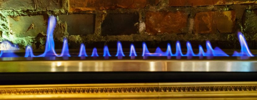 Blaue Flammen eines Gaskamins vor Vintage Steinwand.