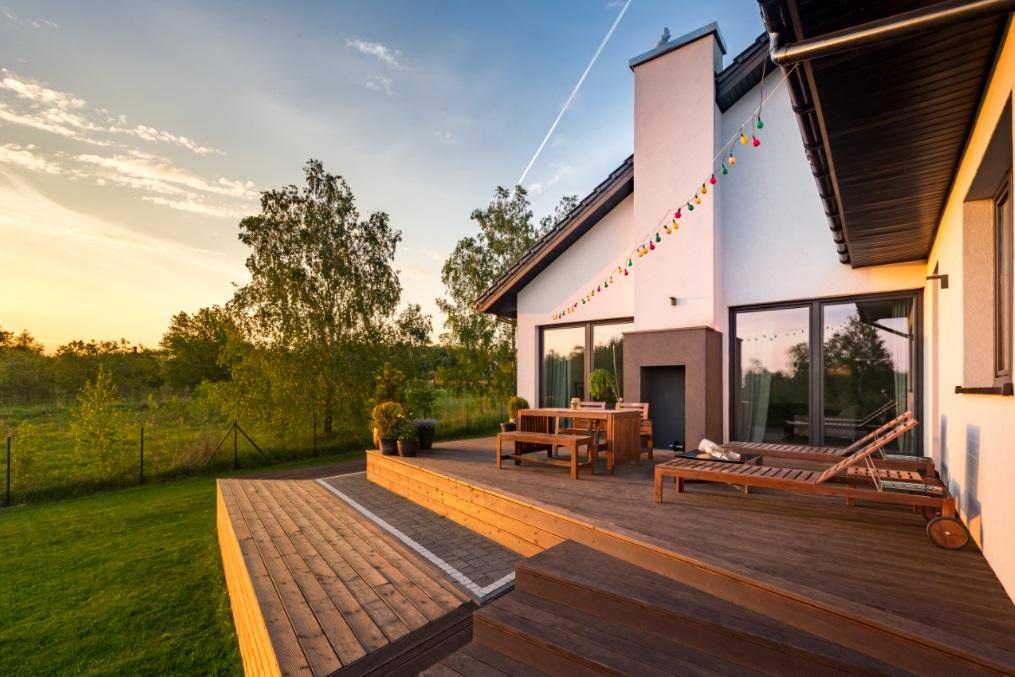 Wunderschöne Holzdielen Terrasse mit zwei Ebenen in grüner Landschaft vor einem malerischen Himmel bei Sonnenuntergang.