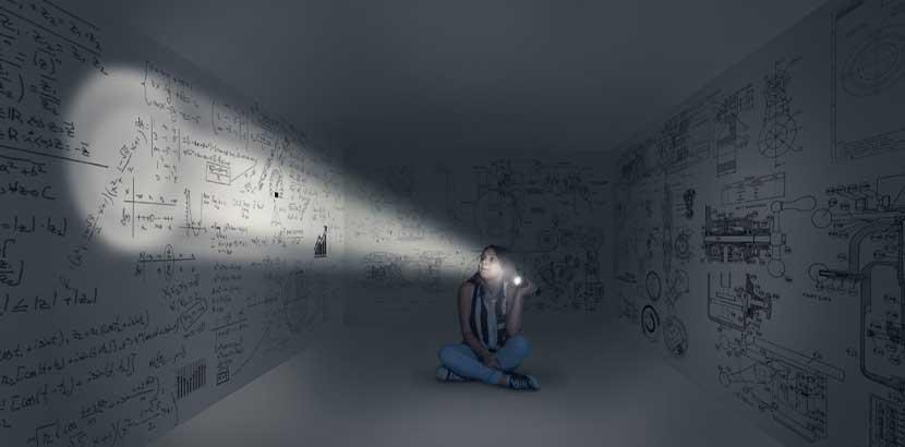 Junges Mädchen, das in einem dunklen Raum mit Rätseln an den Wänden sitzt. Indoor Aktivitäten Wien.