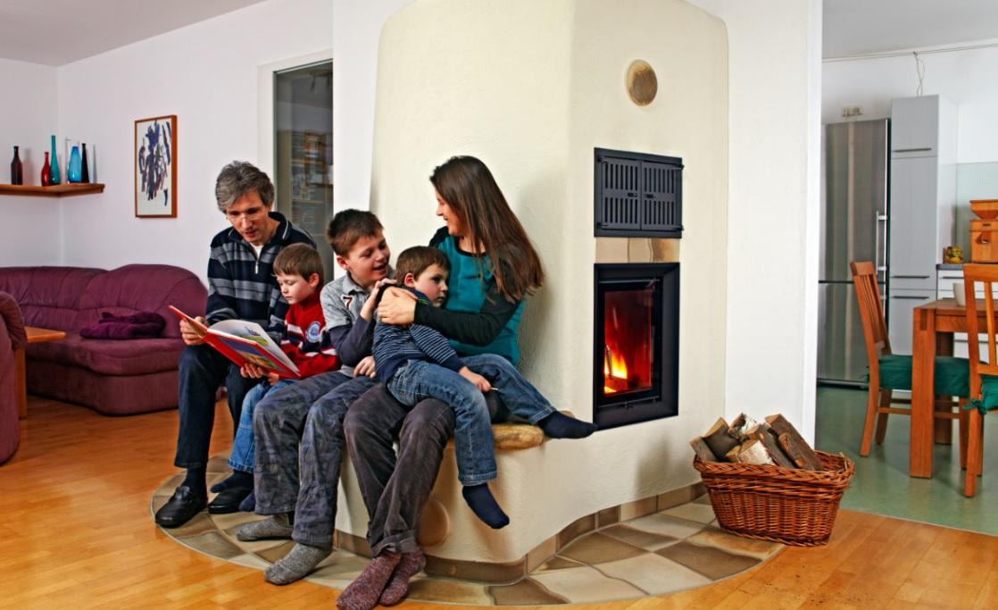 gl ckliche familie mit drei kindern die es sich auf der sitzbank ihres kachelofens gem tlich. Black Bedroom Furniture Sets. Home Design Ideas