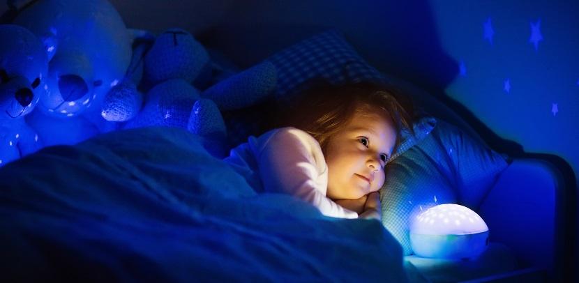 Mädchen liegt im Bett mit Nachtlicht