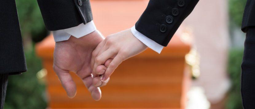 Hände von zwei Menschen, die sich gegenseitig Beistand leisten bei einer Bestattung und anschließend gemeinsam zum Leichenschmaus laden. Leichenschmaus Kosten Wien.